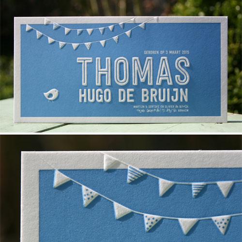 Blauw geboortekaartje voor Thomas met vlaggetjes in een preeg.