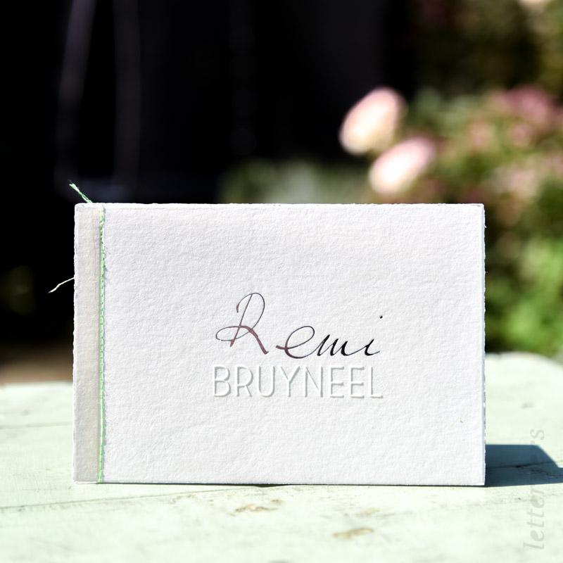 Handgeschreven kaart met een folie en preeg, en een stiksel aan de zijkant.