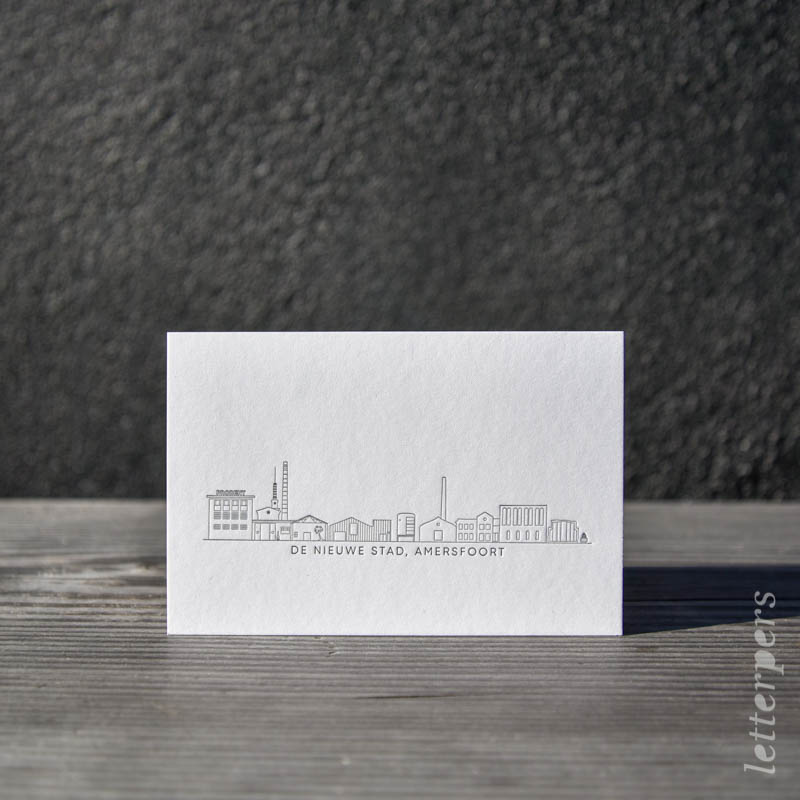Letterperskaart met een kleur, verdiept gedrukt met daarop de skyline van Amersfoort.