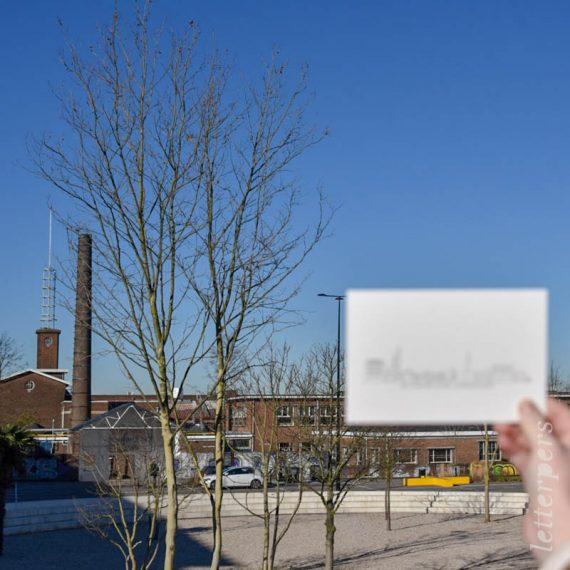 Letterperskaart met de skyline van Amersfoort op de achtergrond. Hierop is de kaart gebaseerd. Focus op gebouwen.