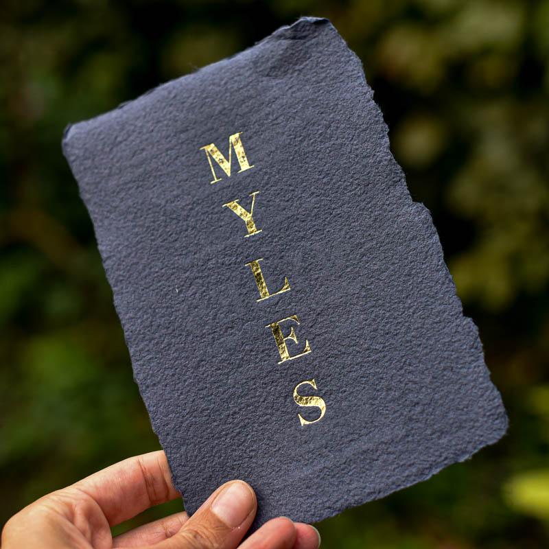 donkerblauw papier met goudfolie als geboortekaartje